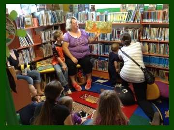 Image, Kathy Frye looks motherly and comfortable as she holds up a storybook and reads to a small cr