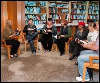 Image, seven people sit in a half-circle of chairs,  holding books & talking.