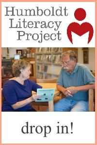 Image, two adults talk at a library table, one holding a magazine, under the literacy logo.