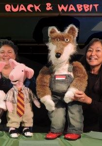 Image, puppeteers hold the big, friendly wolf and pig puppets.