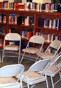 image, chairs in a circle in front of shelves of books.