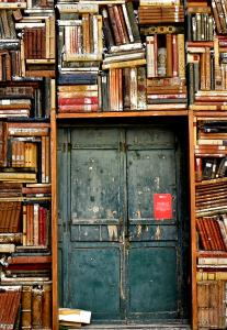 Photo, a double door in a fascinating wall of piled books.