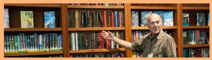 Image, a grey haired man points to a book among others on full wooden shelves.