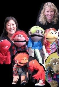 Image, two smiling human faces and many near-lifesized puppets pose for a photo.