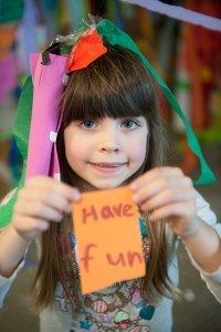 A girl about six years old holds a piece of paper that says 'have fun.'