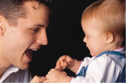 Photo showing a father and baby engaged and happy.