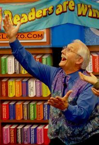 Moustachio'd magician Dale Lorzo gestures to a wall of books.