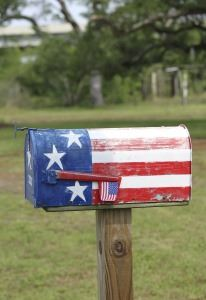 A country mailbox painted in red, white, and blue, with a flag on its flag signal.