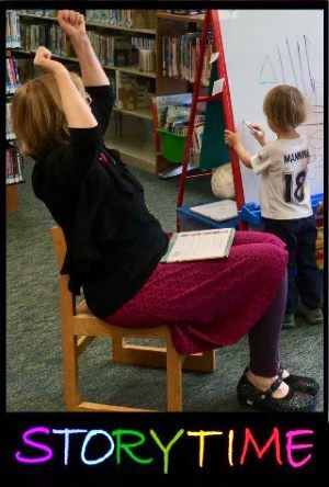 Story time Sue raises her hands in a triumphant gesture as children draw at an easel.