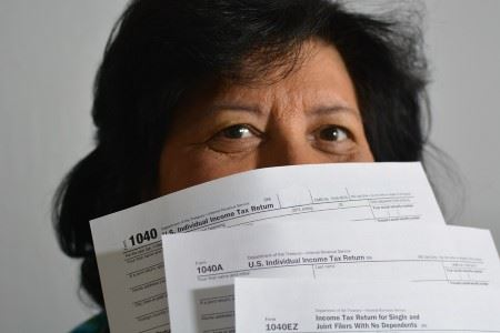 A woman holds three tax forms like a fan in front of her face.