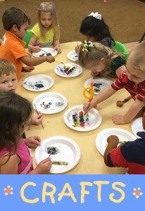 Children seated around a table, using craft materials on paper plates.