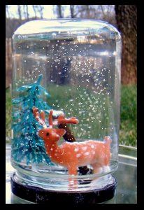 A snow globe made from a jar holds a deer and pine tree in falling snow,