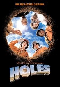 A circle of surprised teen boys look down into a big hole.