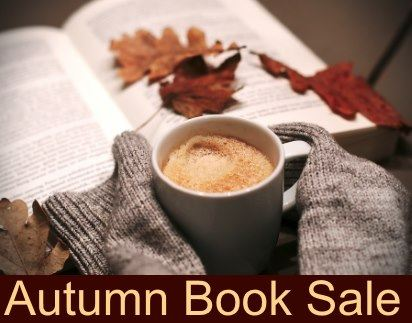 Colorful leaves, a mug of hot frothy coffee, and mittens surround an open book.