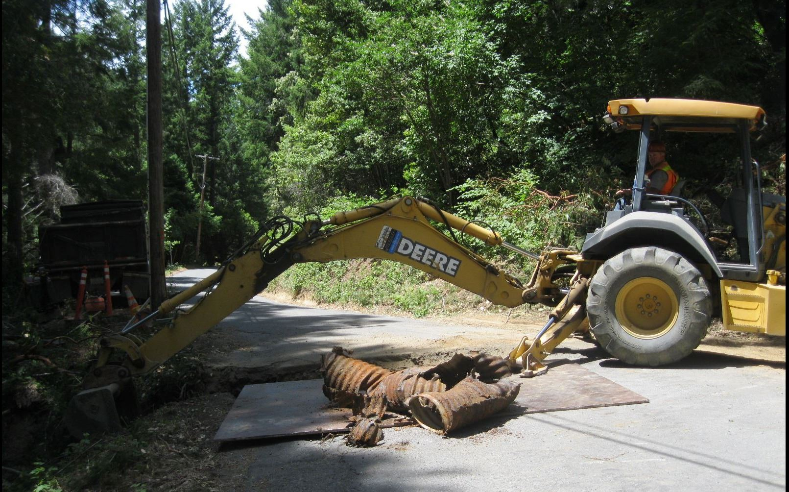 Heavy equipment digging a trench and replacing a damaged culvert