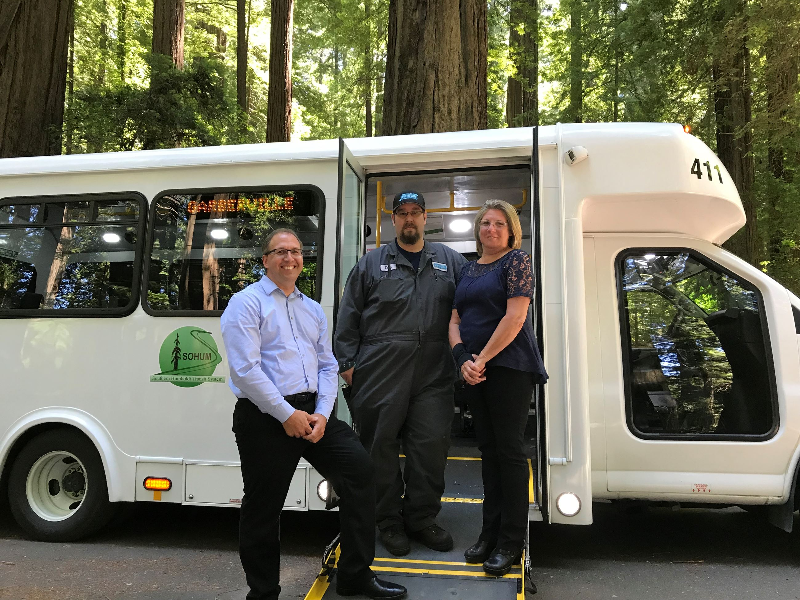 Humboldt Transit Authority bus with three staffers standing in front of it. Tree from the Avenue of
