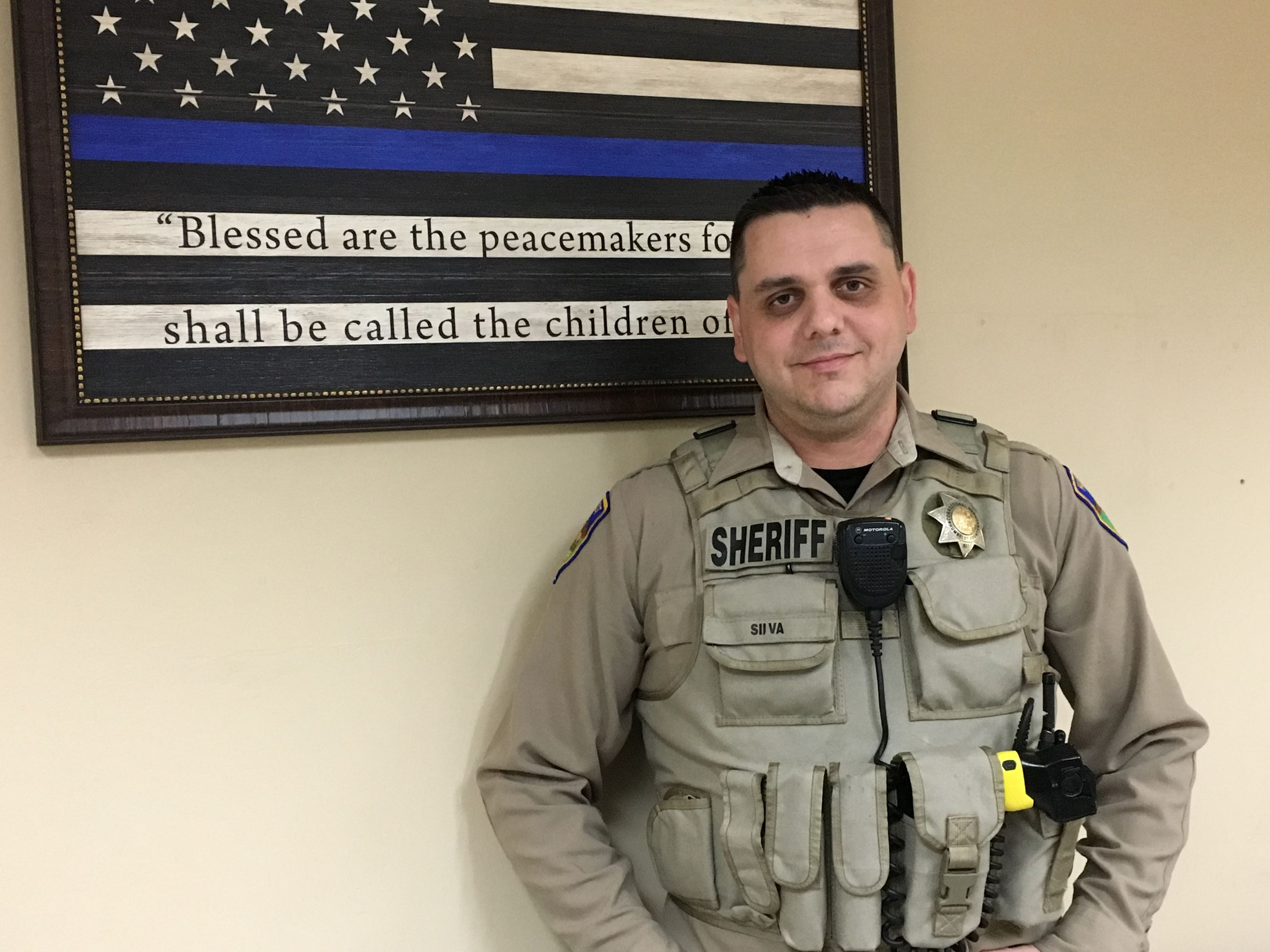 Correctional Deputy Silva in front of a thin blue line flag