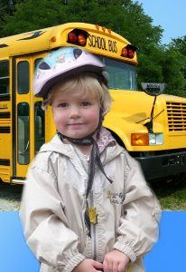 A young child stands near the door of a school bus.