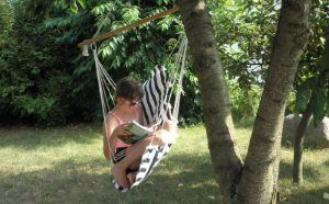 A schoolgirl reads in a hammock chair hanging from a tree in a summer garden.