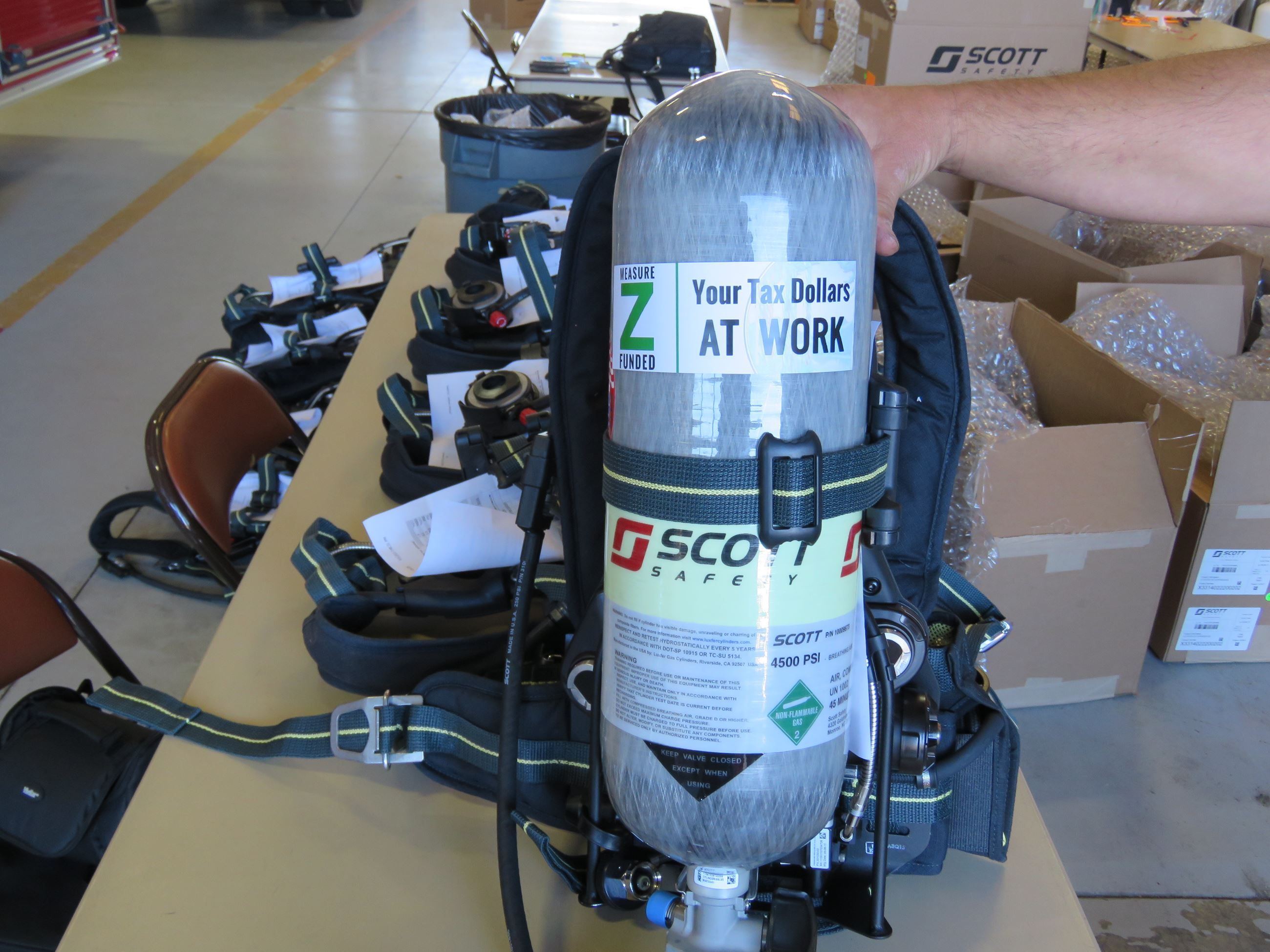 "A fully assembled Self-Contained Breathing Apparatus is stood up, prominently displaying a ""Measu"