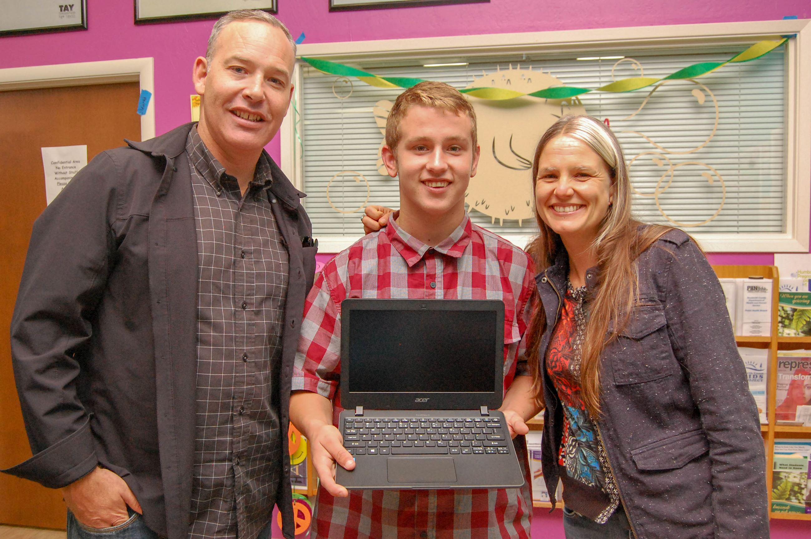Foster youth holding a laptop standing between two support staff