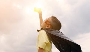 A child dressed as a super hero lifts a library card toward the sun.