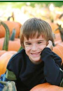 Photo - two boys in a pumpkin patch.