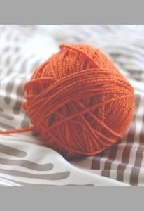 A fat ball of yarn sits on a loose pile of fabric.