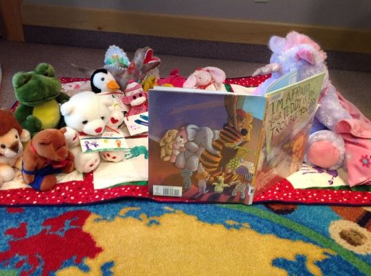 All the little stuffies listen as the Unicorn reads a story.