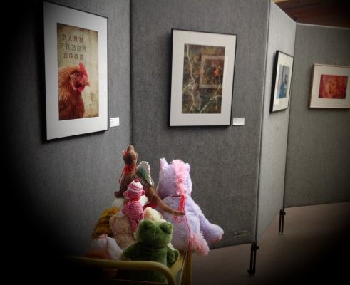 Stuffies ride a cart for a tour of the art gallery, and view a rooster picture.
