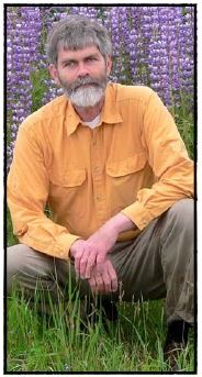 A bearded Jerry Rohde poses in a field of spring wildflowers.