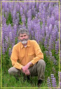 A bearded Jerry Rohde goes to one knee amid a hillside covered in lupin blossom.