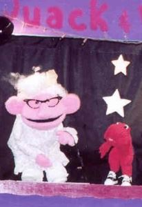 A little furry red puppet talks to an elderly puppet with a wrinkled pink face.