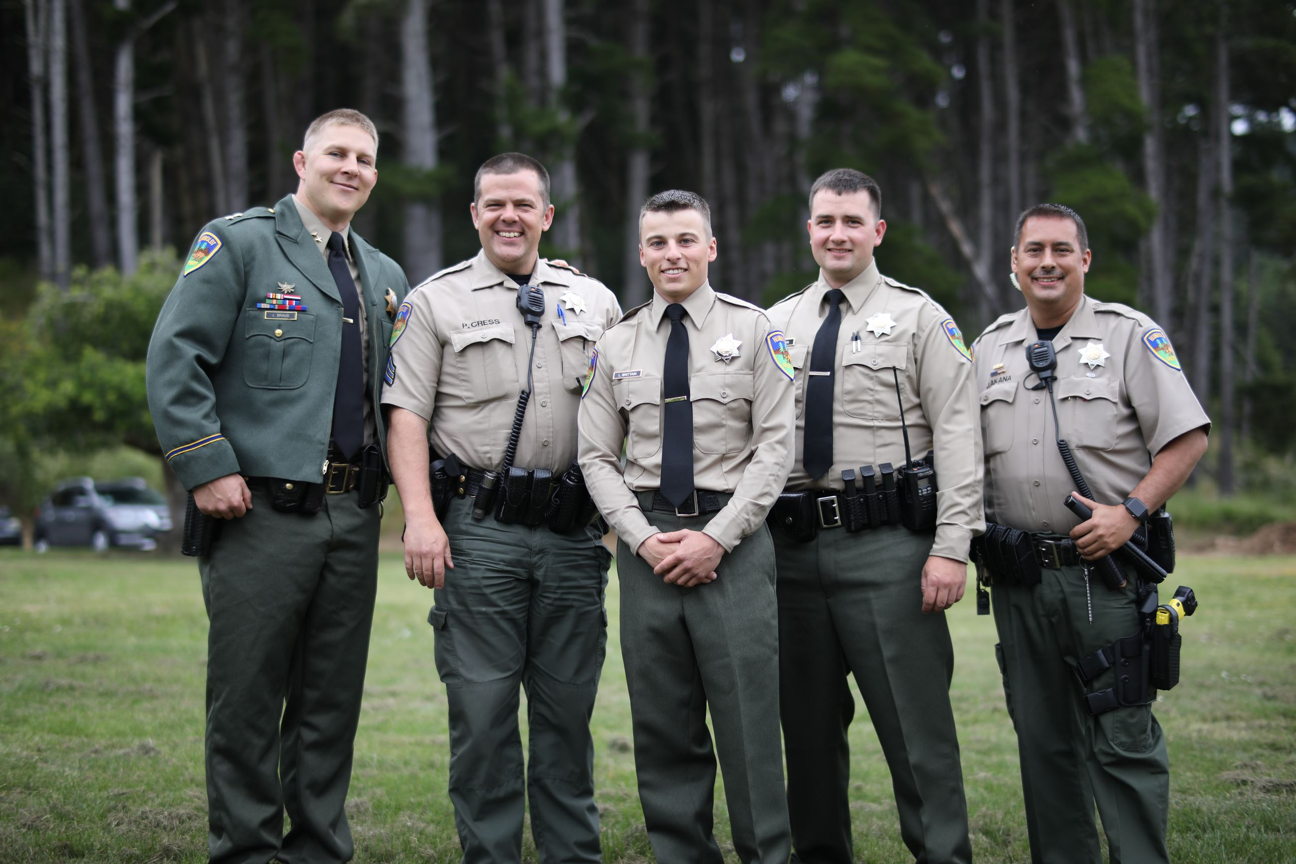 Five deputy sheriffs smiling for a photo in a field