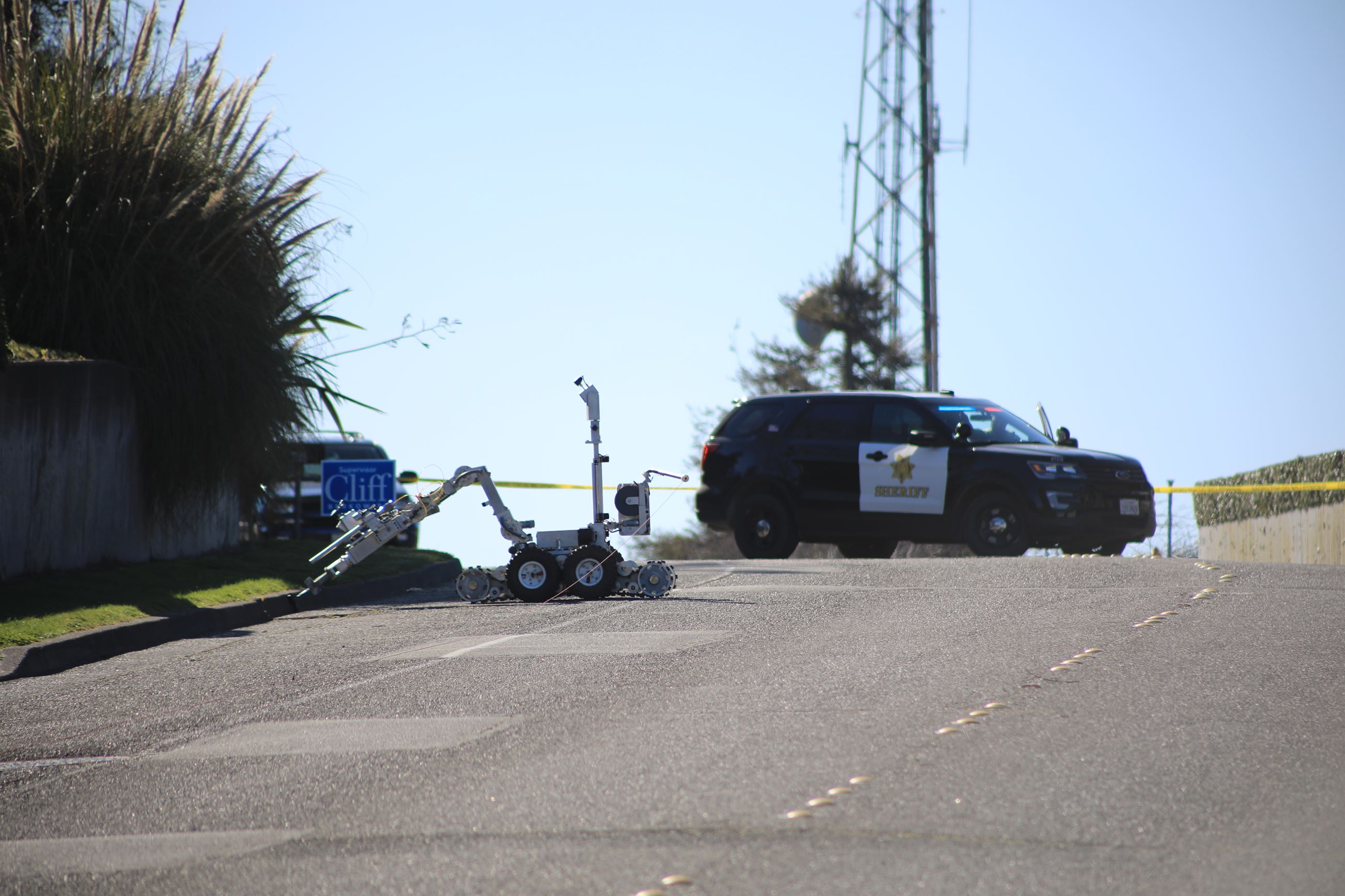 An EOD Robot investigates a suspicious object with a sheriff patrol car in the background
