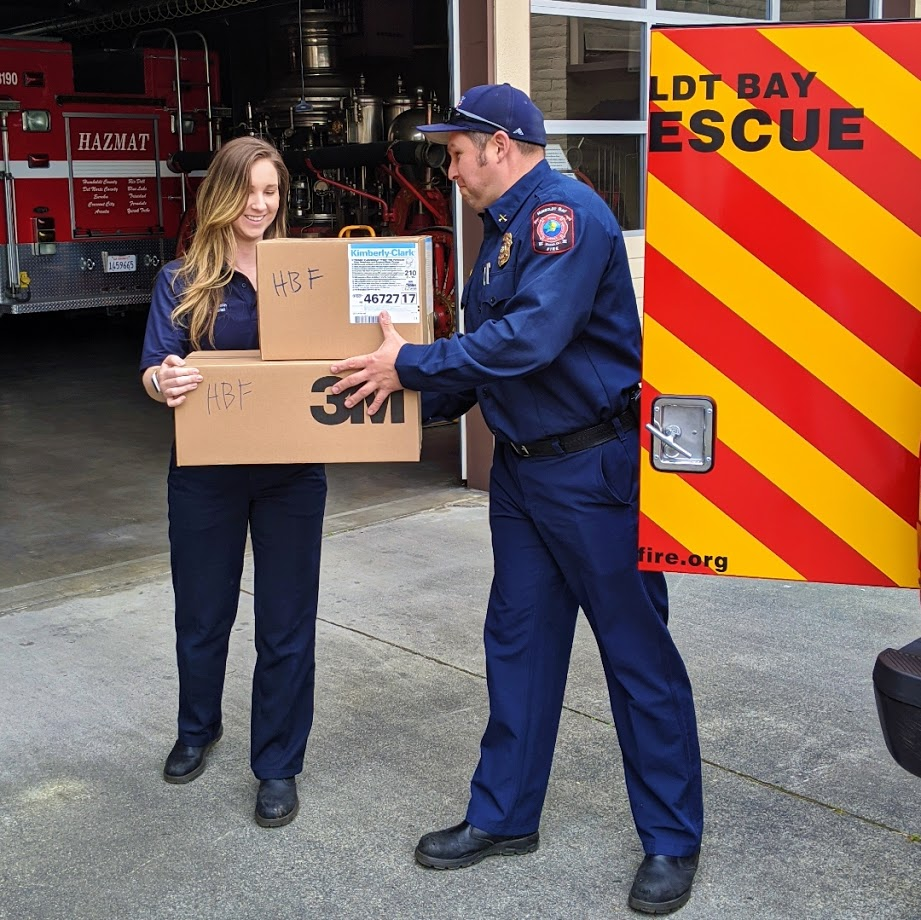 Battalion Chief Nick Launius hands off boxes of much-needed gear to Community Risk Reduction Special