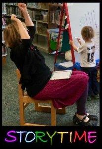 Ms. Sue of Arcata Library raises her arms in an exciting story moment.