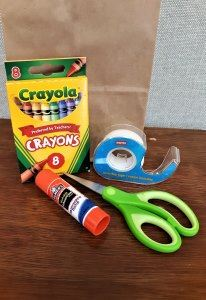 A bag with tape, scissors, glue stick, and small crayon box.