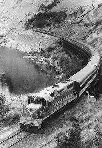 A train rounds a bend along the river, as crumbling cliffs tower above.