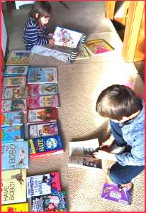 Two children explore the many books spread around them on the floor.