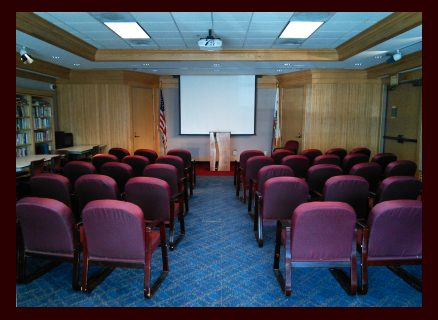 Photo showing a room full of padded chairs with a podium and  movie screen at the front.