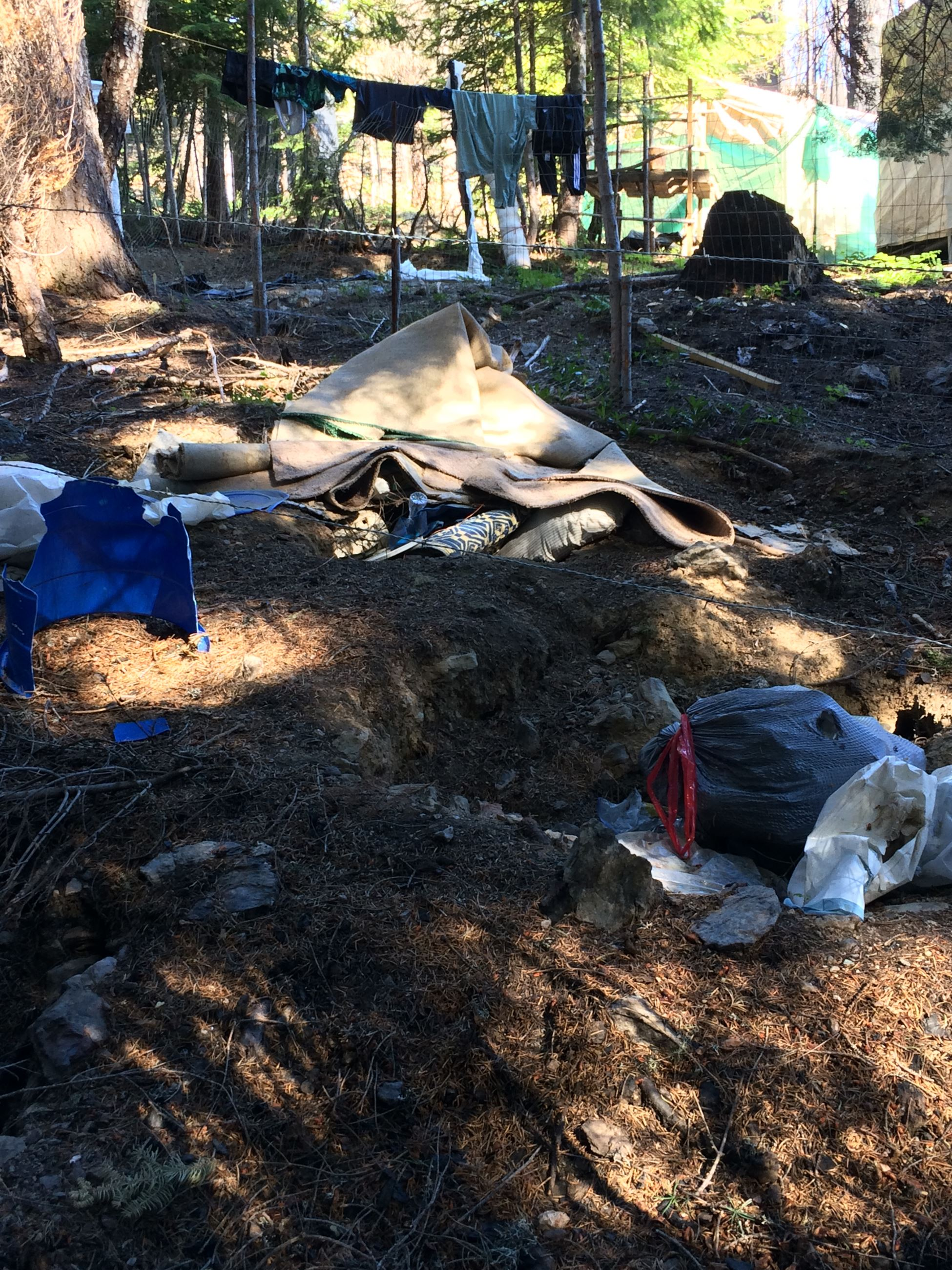 blankets, clothing and trash bags strewn on property