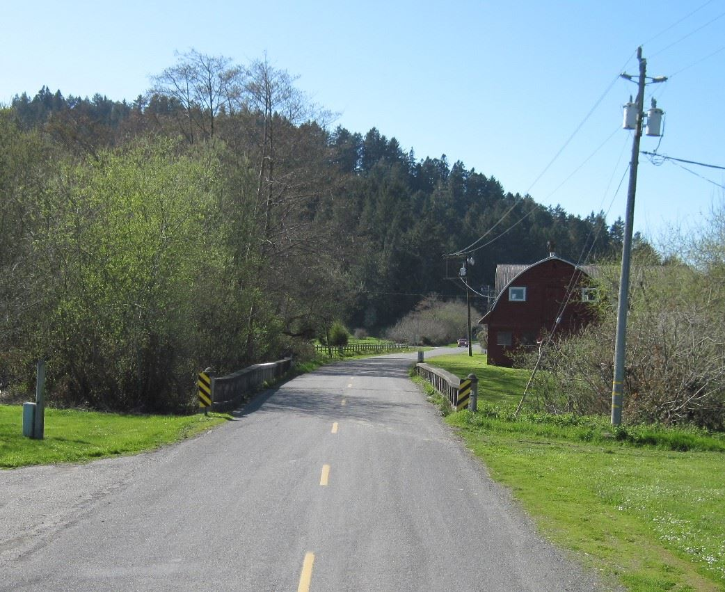 Williams Creek Bridge with red barn on right side of road