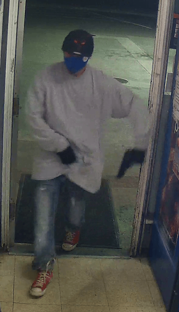 A man wearing a sweatshirt, jeans, hat, and face mask brandishes a firearm as he enters store.