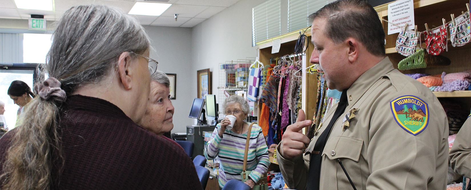 Sheriff's Captain speaks with two women during a Coffee with the Cops event