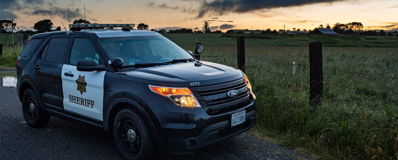 Sheriff's patrol car parked in front of a field during sunset