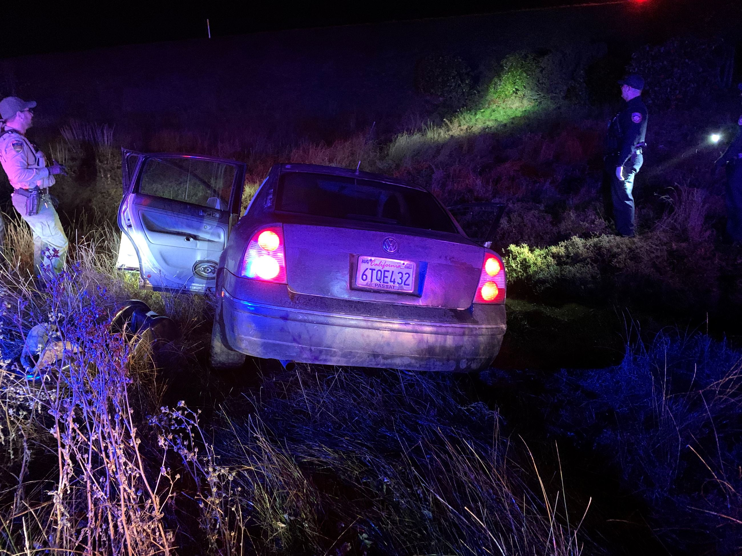 Deputies stand nearby a vehicle that has crashed into the marsh