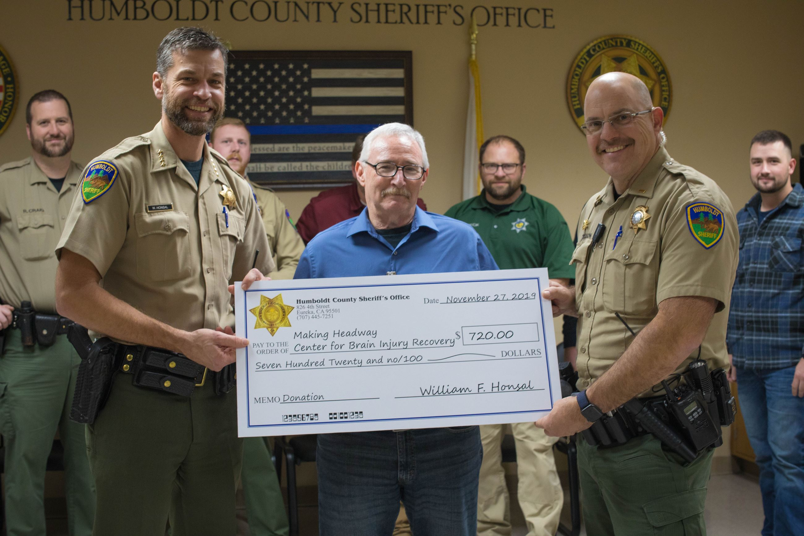 Sheriff Honsal and Lt. Musson present a check to a Making Headway representative