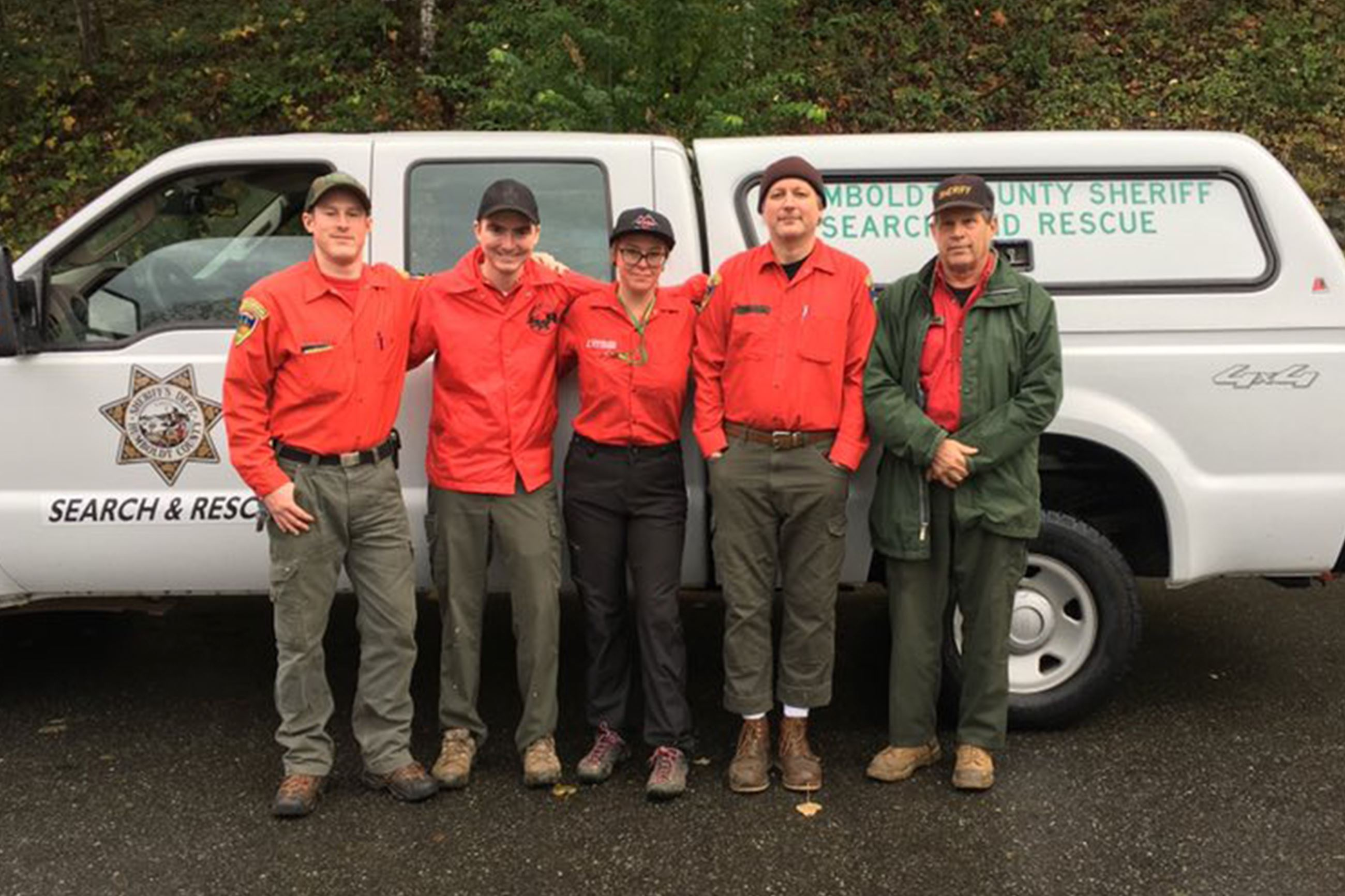 Five search and rescue members stand in front of a truck