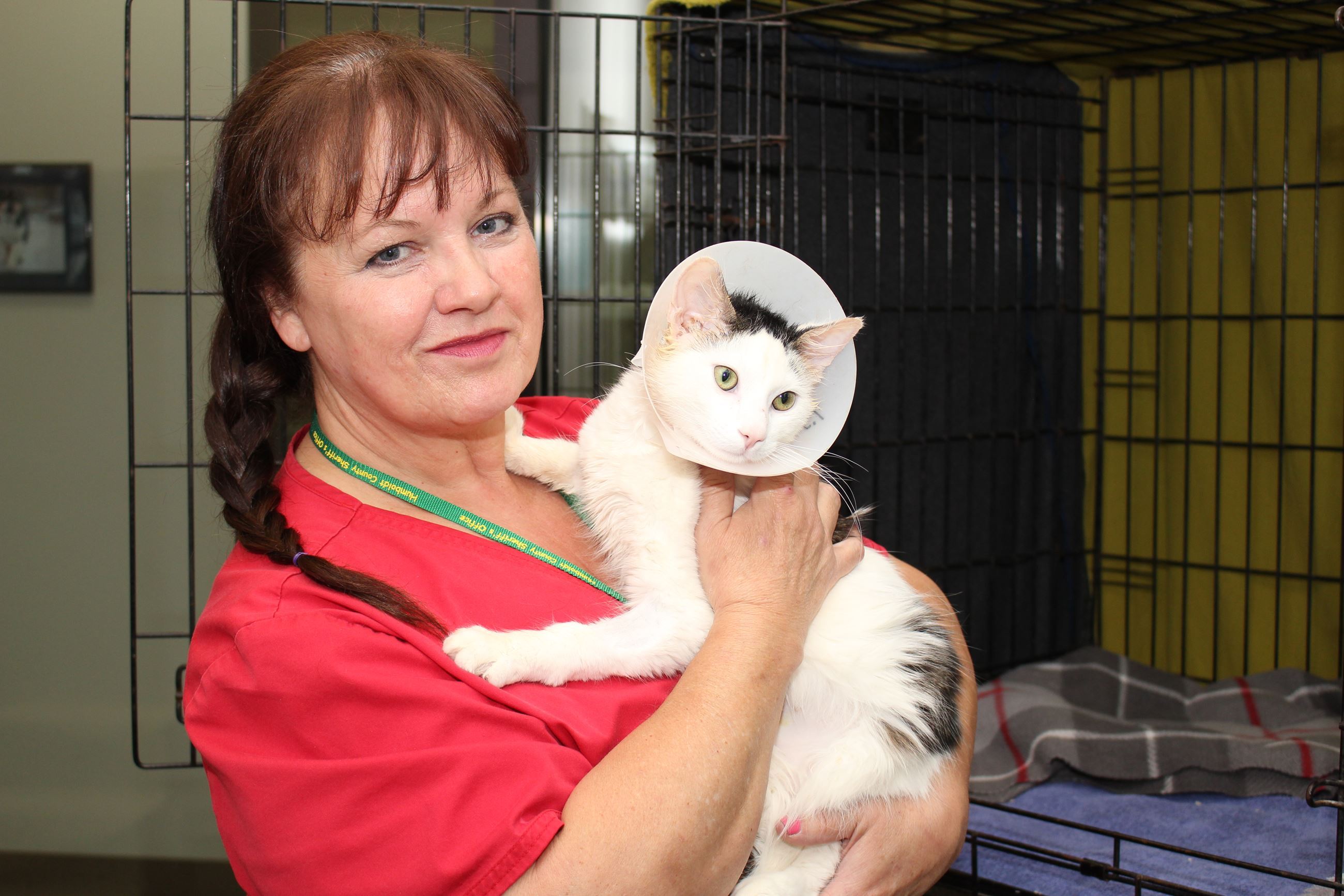 Female Animal Shelter Attendant holds a Cat